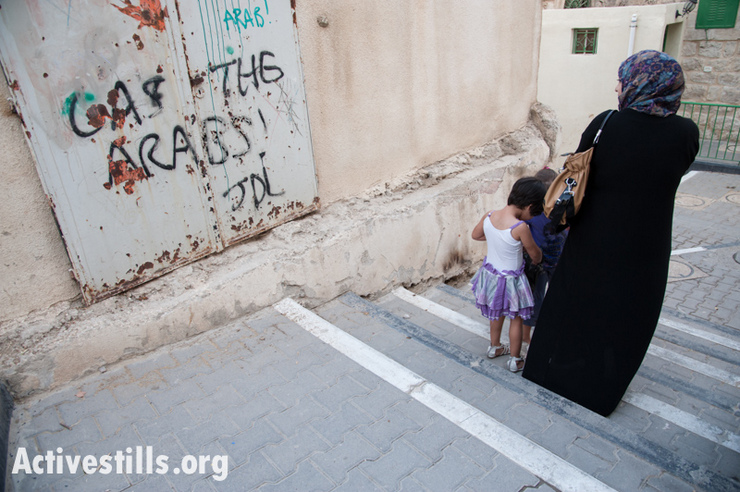 "A Palestinian woman and children pass the slogan ""Gas the Arabs! JDL"" spray-painted on an exterior wall of the Cordoba School near Shuhada Street, Hebron, October 22, 2012. (photo by: Ryan Rodrick Beiler/Activestills.org)"