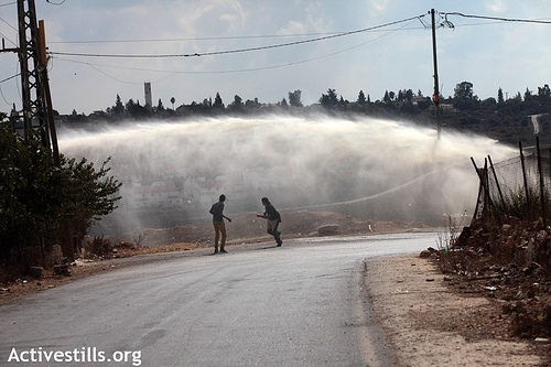 "Palestinian youth run from the ""skunk"", a foul-smelling liquid sprayed by the Israeli army against protesters during the weekly protest against the occupation in the West Bank village of Nabi Saleh, October 5, 2012. (photo: Anne Paq/Activestills.org)"