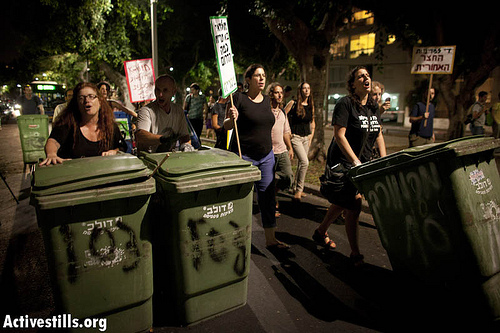 Activists take part in a march from center to South Tel Aviv protesting the discrimination of the city's southern neighborhoods, on October 9, 2012. During the march, organized by Power to the Community, activists took garbage cans from the city center and moved them to the south, to protest of the lack of sanitation services there. Power to the Community is a new action group of both Israelis and refugees in South Tel Aviv. (photo: Oren Ziv/ Activestills.org)