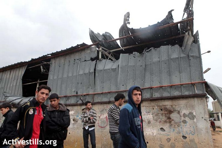Palestinians gather in front of a damaged building where Israeli shelling killed four Palestinians and injured more than 20 the day before, in the al-Shoja'iya neighborhood east of Gaza City , November 11, 2012. (photo by: Anne Paq/Activestills.org)