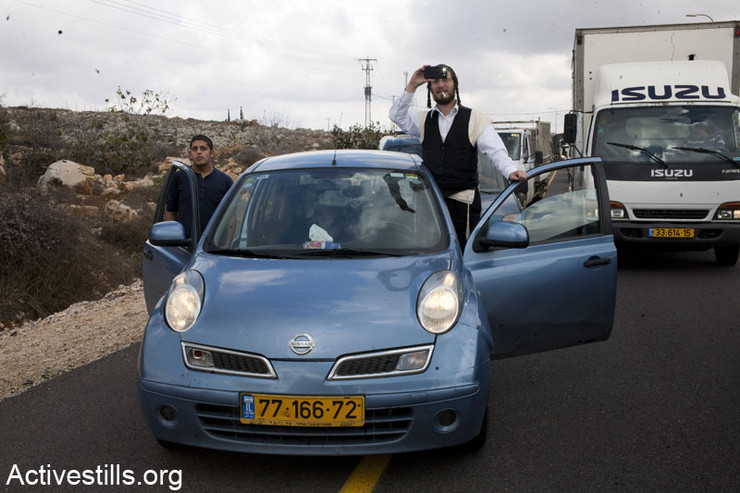 An Israeli settler uses his cell phone to take photos as Palestinian, Israeli, and international activists block Road 60 during a day of coordinated demonstrations blocking roads throughout the occupied territories, November 14, 2012. (photo: Keren Manor/Activestills.org)