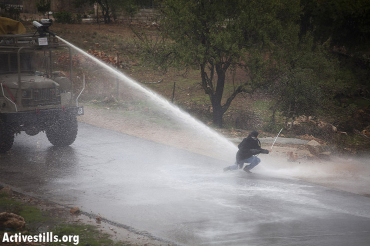 """Nariman Tamimi, sister of Rushdi Tamimi, killed by the Israeli army last Saturday, gets sprayed by the """"Skunk,"""" a foul-smelling liquid sprayed by the Israeli army, during the weekly protest against the occupation in the West Bank village of Nabi Saleh, November 23, 2012. (Photo by: Oren Ziv/ Activestills.org)"""