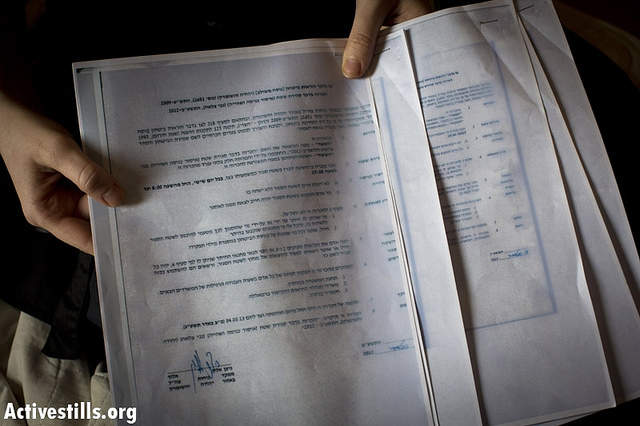 An Israeli activist displays a closed military zone order which, given to her by Israeli policemen at 6 a.m. in her Tel Aviv home, November 11, 2012. (photo: Activestills)