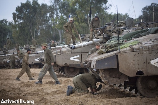 Israeli soldiers inspect their tanks on the Gaza border during Operation Pillar of Defense in 2012. (Photo by Activestills.org)