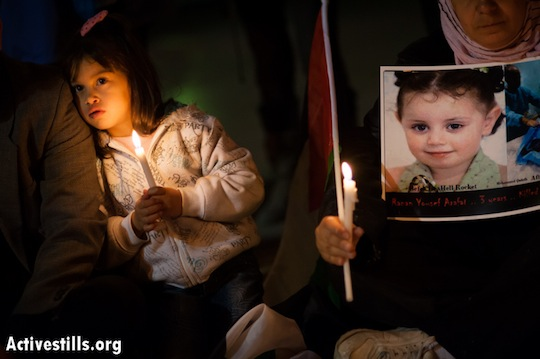 A girl holds a candle next to a photo of 3-year-old Ranan Yousef Arafat, who was killed by Israeli airstrikes in Gaza, as Palestinians gathered in Bethlehem's Manger Square to mourn the victims of Israeli military strikes and to call for an end to the escalation of violence, November 17, 2012.