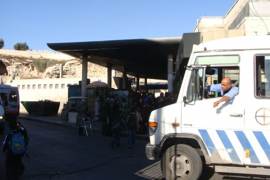 "Outside of one of the entrances of the ""Central Bus Station"" in East Jerusalem. The driver hangs out the window to make sure there are no children crossing in front of the small bus."