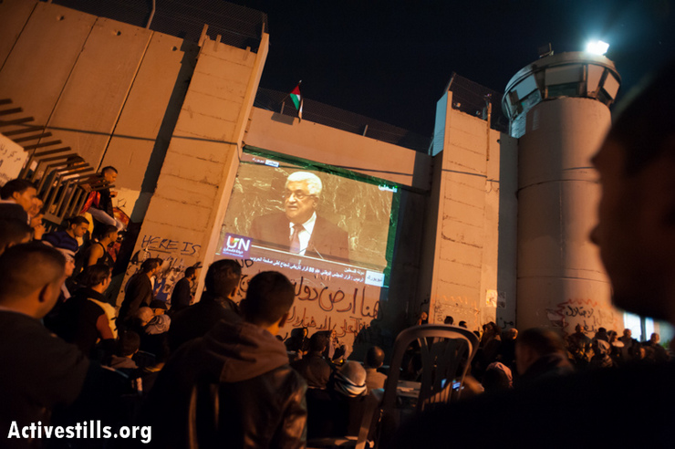 "Hundreds of Palestinians gather to watch the speech by Prime Minister Mahmoud Abbas in the bid for Palestine's ""nonmember observer state"" status at the United Nations, projected on the Israeli separation wall in the West Bank town of Bethlehem, November 29, 2012. Hours later, the UN General Assembly voted 138-9 in favor of the upgraded status for Palestine, with 41 nations abstaining. (Photo by: Ryan Rodrick Beiler/Activestills.org)"