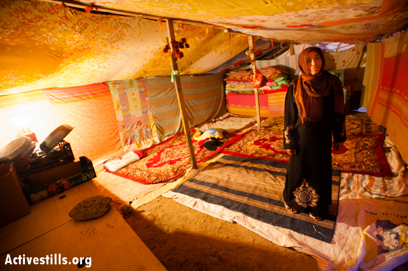 A Jahalin Bedouin woman stands inside her tent, which like all the structures in her village which are under demolition orders by Israeli authorities.