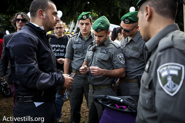 Border police checking the ID card of a Palestinian during the human rights march.(photo: Shachaf Polakow/Activestills)