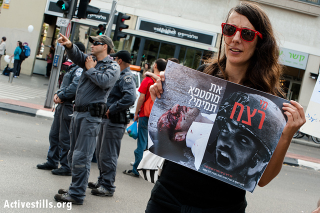 """An Israeli activist at the annual human rights march in Tel Aviv holds a poster asking """"Who Killed Mustafa Tamimi?"""" December 7, 2012. Tamimi was killed on December 9, 2011, when he was shot in the face with a tear gas canister at close range by Israeli soldiers. Also pictured on the poster is Lieutenant Colonel Shay Ben Yshai, the direct commander of the soldier who killed Tamimi. No one responsible for Tamimi's death has been brought to justice to this day. (photo: Ryan Rodrick Beiler/Activestills)"""