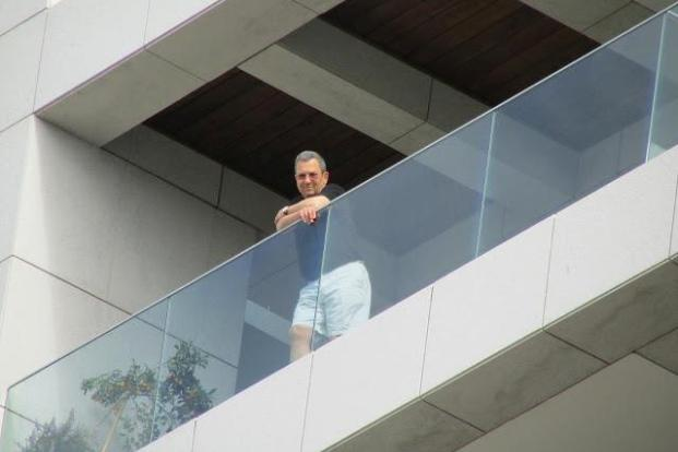 Israeli Defense Minister Ehud Barak, in shorts and a T-shirt, watching over the annual Human Rights March, passing beneath his house in Gindi Tower, central Tel Aviv. (photo: Sebastian Wallerstein)