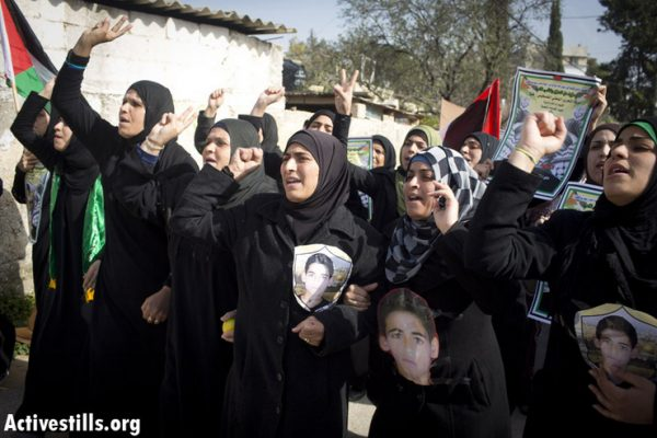 Palestinian women holding pictures of Samir Awad, during a protest against the occupation, Budrus, January 18, 2013. (Oren Ziv/Activestills.org) Awad had been shot and killed three days earlier by IDF soldiers.