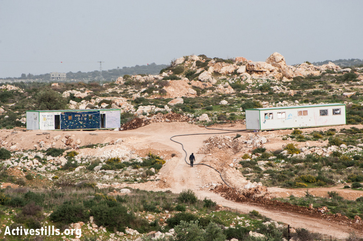 Two caravans form a new Israeli settler outpost on land belonging to the West Bank village of Jayyous, January 28, 2013. The structures were placed just one week prior, and are already being connected to water lines from the nearby settlement Zufin. The location was likely chosen to disrupt implementation of a 2009 Israeli court decision to re-route the separation barrier, returning a portion of Jayyous's land to the other side of the fence, including the area that the outpost now occupies. (Photo by: Ryan Rodrick Beiler/Activestills.org)