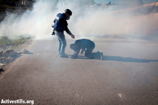 A press photographer helps his colleague which was hit from a tear gas canister shot by Israeli soldiers, during a protest against the occupation in the West Bank village of Nabi Saleh, December 23, 2011 (Photo by: Oren Ziv/ Activestills.org)