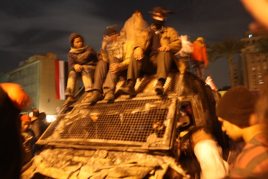 Black Bloc and Tahrir youth celebrate atop a torched, commandeered police truck in the center of the square. (photo: Jesse Rosenfeld)