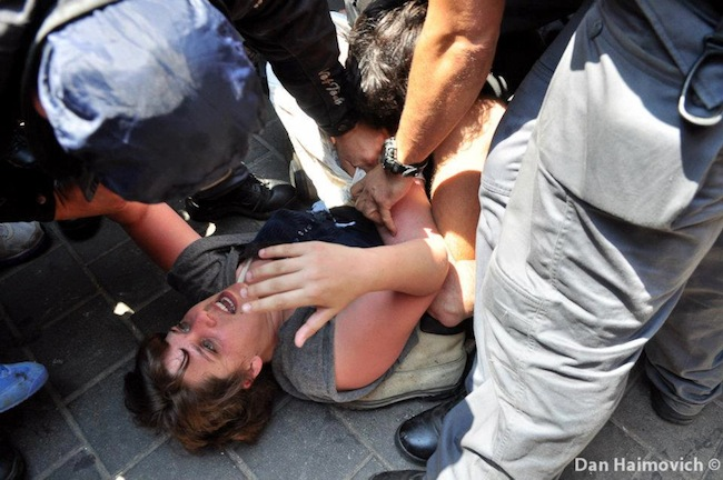 J14 leader Daphni Leef held down on the ground as she is arrested by police officers (photo: Dan Haimovich)