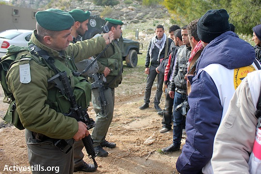 """Soldiers prevent activists from reaching the main gate of the E1 area where the Palestinian outpost """"Bab Al-Shams"""" is located, January 12, 2013. (photo: Ahmad Al-Bazz/Activestills)"""