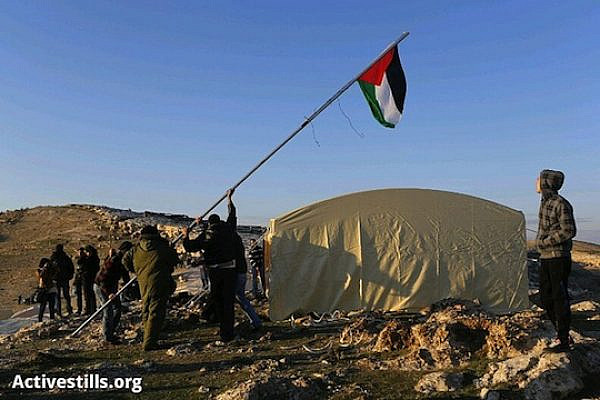 "Palestinian activists lifting the Palestinian flag in the ""Bab Al-Shams"" village. (photo: Oren Ziv/Activestills)"