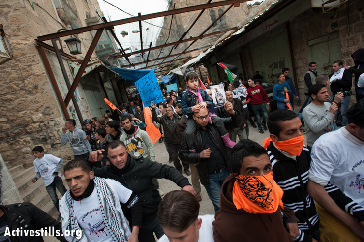 During a protest against the closure of the Shuhada Street, Palestinians march under wire screens placed above the street to protect Palestinians from stones and trash thrown by Israeli settlers occupying buildings above, in the West Bank city of Hebron, February 22, 2013. (Photo by: Ryan Rodrick Beiler/Activestills.org)