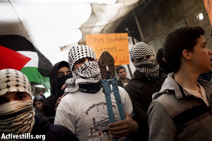 A demonstrator carries bolt cutters during a march against the continued closure of Shuhada Street to Palestinians, in the West Bank city of Hebron February 22, 2013. (Photo by: Oren Ziv/Activestills.org)