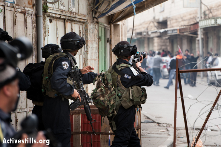 An Israeli soldier aims a tear gas launcher at demonstrators during a protest against the closure of the Shuhada Street to Palestinians, in the West Bank city of Hebron, February 22, 2013. (Photo by: Ryan Rodrick Beiler/Activestills.org)