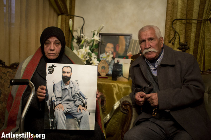 "Laila and Tariq Issawi, Samer Issawi's parents, in their home, February 2, 2013. Samer Issawi is extremely unwell, and is being held in the prisoners medical center; he has been on hunger strike for 191 days. The family was prevented from attending his last hearing at the ""Shalom"" court in Jerusalem, on December 18, 2012. (Photo by: Oren Ziv/Activestills.org)"