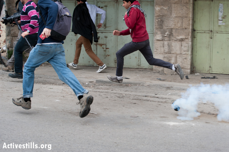 Demonstrators flee tear gas launched by Israeli forces during a protest against the closure of the street to Palestinians, in the West Bank city of Hebron, February 22, 2013. (Photo by: Ryan Rodrick Beiler/Activestills.org)