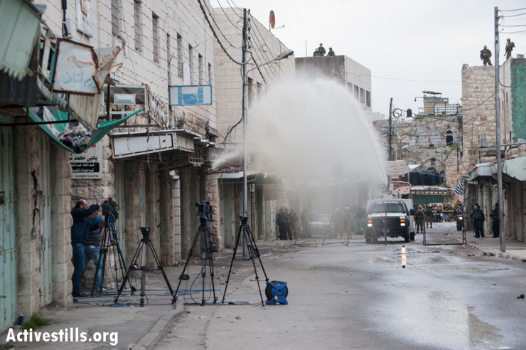 "Israeli forces target members of the media with the ""skunk truck"", a water canon loaded with a foul-smelling liquid, during a protest against the continuing closure of Shuhada Street to Palestinians in the West Bank city of Hebron, February 22, 2013. (Photo by: Ryan Rodrick Beiler/Activestills.org)"