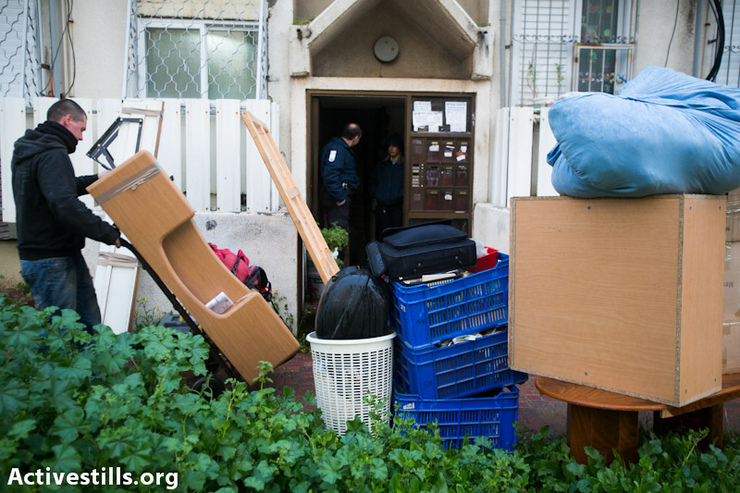 Movers clear the belongings of 61-year-old Rivka Levi, after she was forcefully evicted from her public housing flat owned by Amidar company, Petah Tikva, January 31, 2013. Four activists were arrested trying to prevent the eviction. (Photo By: Yotam Ronen/Activestills.org)
