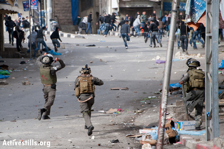 An Israeli soldier throws a sound bomb at fleeing demonstrators during a protest against the closure of Shuhada Street to Palestinians, Hebron, West Bank, , February 22, 2013. (Photo by: Ryan Rodrick Beiler/Activestills.org)