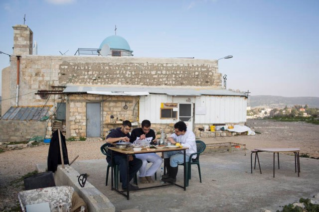 The young villagers of the New Iqrit enjoying lunch outside the church (Oren Ziv / Activestills)