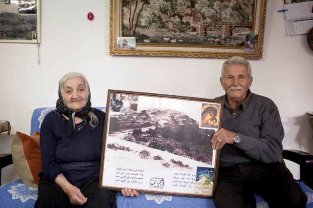 Labeeb and Marth Ashkar holding a picture of the village they were deported from in 1948 (Oren Ziv / Activestills)