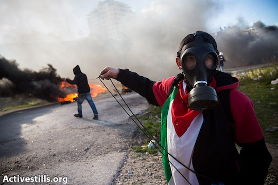 Palestinian youth throw stones during a solidarity protest with the hunger striking Palestinian prisoners jailed in Israeli prisons, outside the Ofer military prison, February 15, 2013. (photo: Activestills)