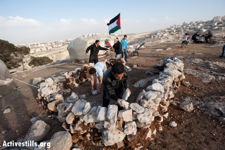 Palestinian activists build a structure from stones and mud in the Bab al Shams protest camp in the E1 area, West Bank, March 22, 2013. (Photo by: Ryan Rodrick Beiler/Activestills.org)