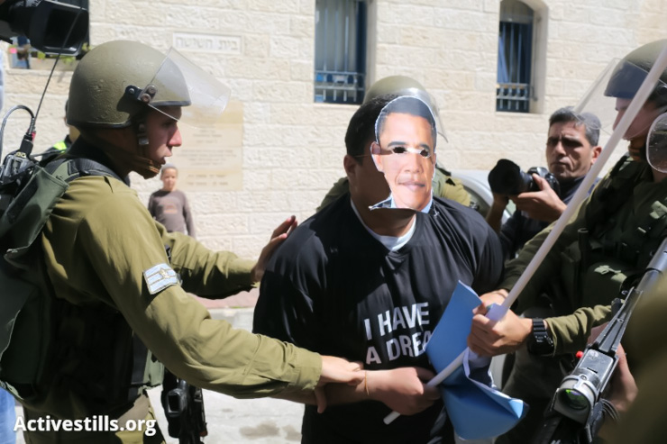 A demonstrator wears an Obama's mask being arrested by Israeli army forces during a demonstration against the planned visit of US President Barack Obama to the West Bank, March 20, 2013. (Photo by: Oren Ziv/Activestills.org)