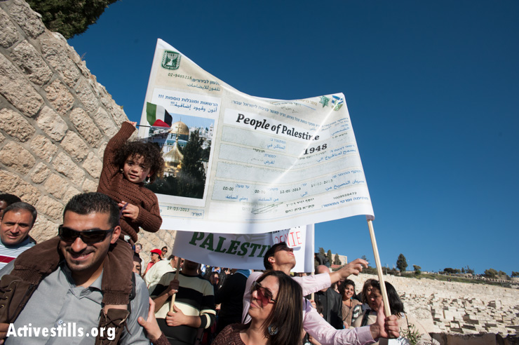 Palestinian Christians carry a mock Israeli permit for entering Jerusalem. All Palestinians living in the West Bank and Gaza are cut off from Jerusalem by the Israeli separation barrier, requiring their residents to obtain special permits to enter.