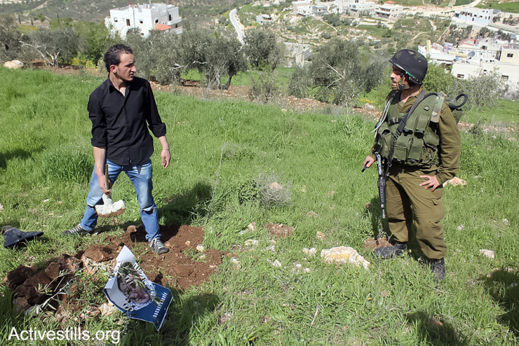 Israeli soldier tries to prevent Palestinian from planting olive trees on land which could be confiscated by the settlement of Yitzhar in Asira AlQibliya village, West Bank, March 11, 2013. All Israeli settlements in the occupied Palestinian territories are illegal under international law. (Photo by: Ahmad Al-Bazz/Activestills.org)