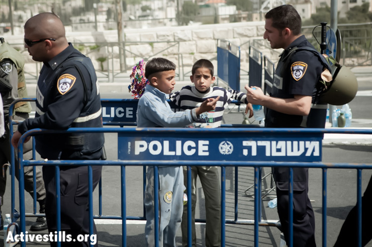 Palestinian children try to exit through a police barricade during the weekly Friday prayer in the Al Aqsa Mosque compound, Jerusalem, March 15, 2013. Israeli police forces allowed only men over the age of 50 to enter Al Aqsa, denying hundreds of people their right to pray a week after clashes between Israeli security forces and Palestinian protesters. (Photo by: Shiraz Grinbaum/Activestills.org)