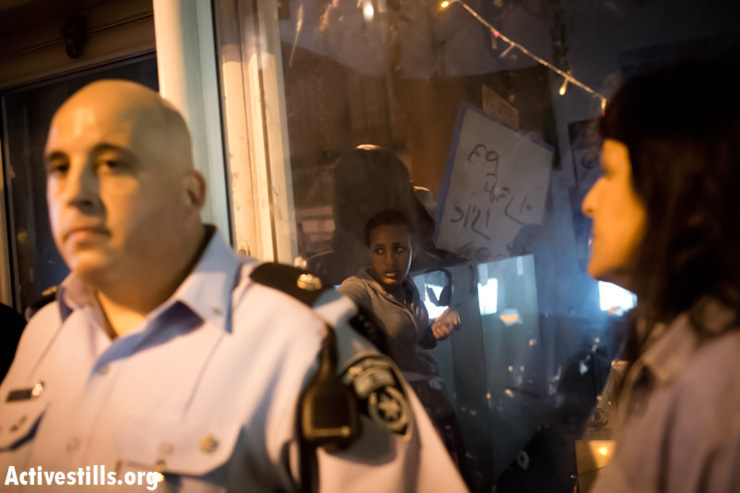 An Eritrean women seeks safety inside an internet cafe owned by immigrants, as police stand guard outside, after Israeli protesters tried to brake in during a protest against African immigrants in south Tel Aviv, March 13, 2013. The protest was held after an African immigrant allegedly broke into a house in south Tel Aviv, stole a phone, and stabbed an Israeli woman earlier that day. (Photo by: Oren Ziv/ Activestills.org)