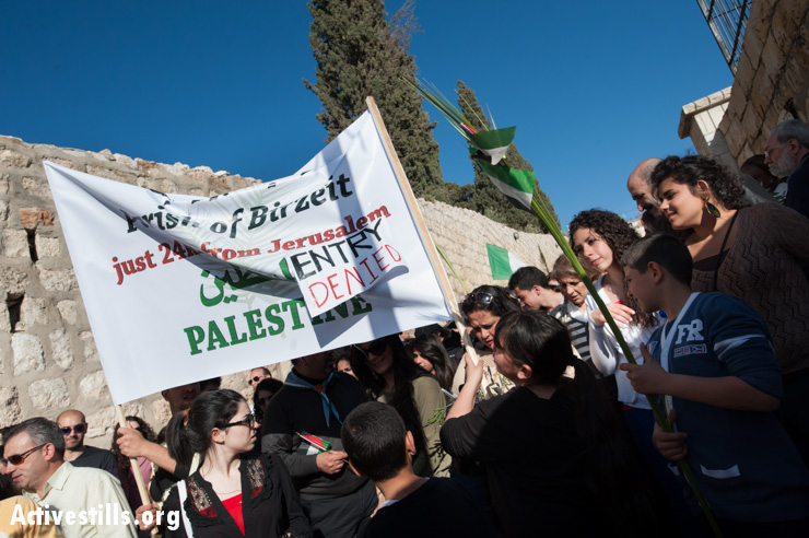 "Palestinian Christians carry a banner for the West Bank town of Birzeit with a sign attached reading ""Entry Denied"". This year, residents of Birzeit and several other West Bank communities did not receive the additional permits typically issued for religious seasons in time to participate in the Palm Sunday celebration."