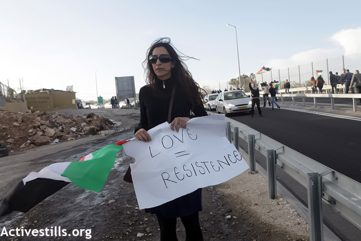 A Palestinian activist holds a sign during an action against the separation policy between Palestinians living in the West Bank married to Palestinians living in Jerusalem or Israel, Hizma checkpoint, West Bank, March 9, 2012. The action, which included a mock wedding, was suppressed by the Israeli army which prevented a bus of activists from reaching the place of the action, as well as a bride from the Jerusalem side. (Photo by: Anne Paq/Activestills.org)