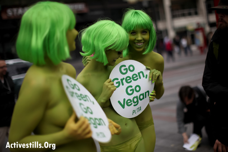 """PETA activists protest in downtown Seattle on Friday, March 15, 2013. The protesters, painted green, carried signs reading """"Go Green, Go Vegan"""". (Photo by: Tess Scheflan/Activestills.org)"""