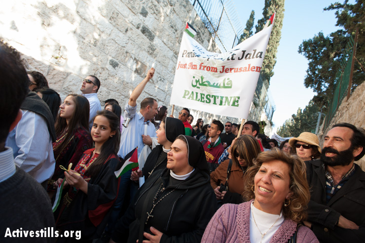 In the annual Palm Sunday procession, Palestinian Christians carry signs naming their West Bank communities, all of which are cut off from Jerusalem by the Israeli separation barrier, requiring their residents to obtain special permits to enter, March 24, 2013. Such restrictions have dramatically reduced the number of Palestinians able to participate in religious traditions of any faith in Jerusalem.