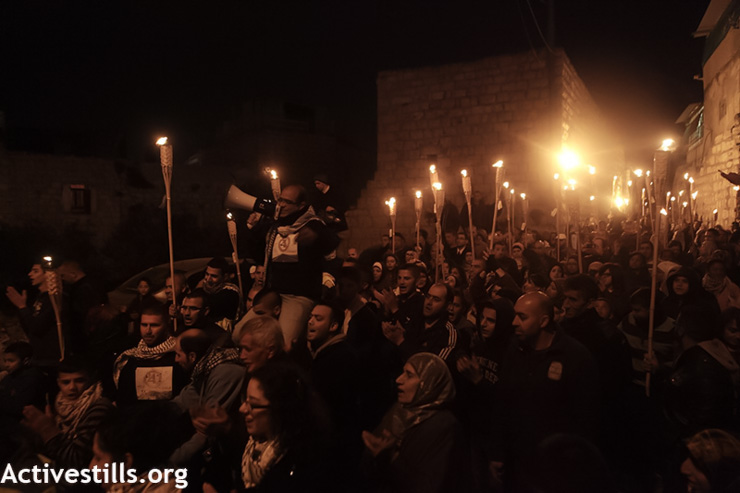Residents of Beit Safafa march with torches to protest the four-lane highway that will cut through their town in East Jerusalem, March 7, 2013. The road is being constructed on privately owned land that had been designated for building homes in the densely populated town, and is being built despite the objections of local residents. The road will connect the various Israeli settlements of the southern West Bank with Jerusalem and is part of an ongoing campaign to isolate and surround the Palestinian neighborhoods of Jerusalem with Israeli settlements. (Photo by: Anne Paq/Activestills.org)