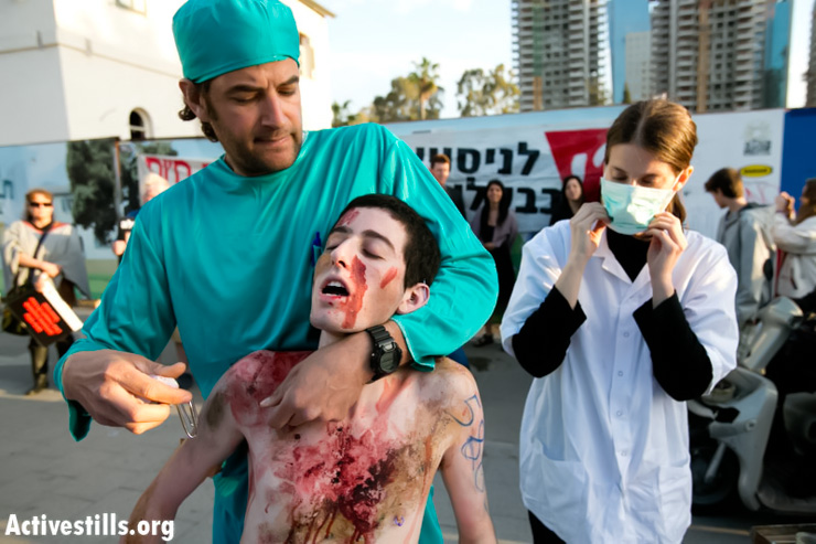 Israeli activists perform in front of the Ministry of Defense in center Tel Aviv as part of a campaign aimed at drawing attention to the pain and cruelty inflicted on laboratory animals during testing by the Israeli army, March 19, 2013. (Photo by: Yotam Ronen/Activestills.org)