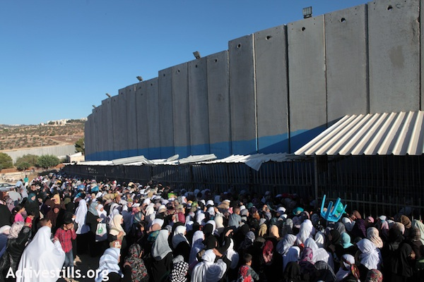 Palestinians wait to get through at checkpoint at the separation wall in Bethlehem [file photo], (Photo: Activestills.org)
