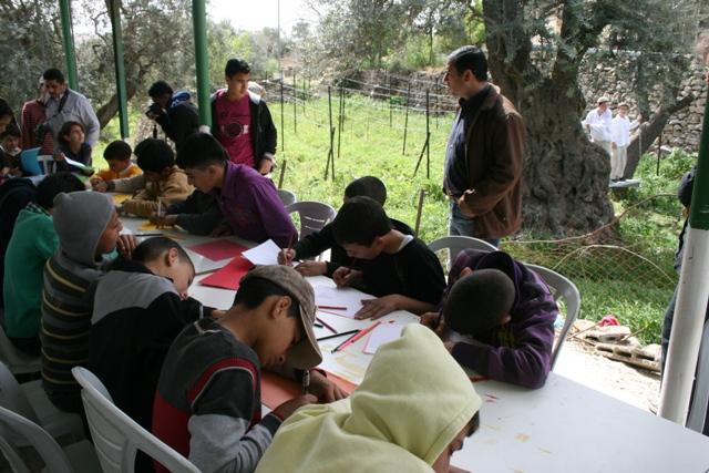 Palestinian children writing the US president. Settler children watching (Haggai Matar)