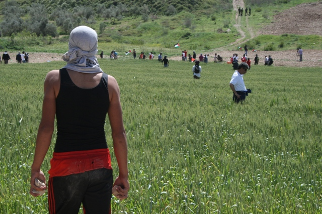 Palestinian youth watching soldiers with stones in his hands (Haggai Matar)
