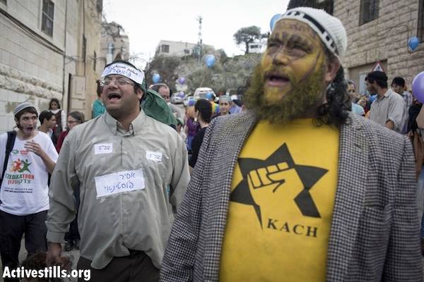 Israeli settlers at the Hebron Jewish settlement's Purim parade on the city's Shuhada Street. Itamar Ben Gvir (L), is dressed as a hunger-striking Palestinian prisoner. February 24, 2013 (Activestills.org)