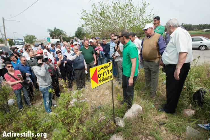 Palestinian Israelis plant a sign marking the destroyed village of Al-Ruways.